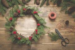 Στεφάνι Χριστουγέννων φιαγμένο από κομψούς κλάδους με τα μούρα ελαιόπρινου στον ξύλινο πίνακα Εργαστήριο στεφανιών Τοπ όψη Στοκ φωτογραφίες με δικαίωμα ελεύθερης χρήσης