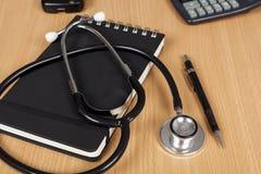 Στηθοσκόπιο γιατρών που βάζει σε ένα σημειωματάριο σε ένα γραφείο Στοκ Φωτογραφίες