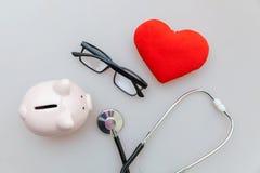 Στηθοσκόπιο εξοπλισμού γιατρών ιατρικής ή phonendoscope piggy γυαλιά τραπεζών και κόκκινη καρδιά που απομονώνονται στο άσπρο υπόβ στοκ φωτογραφίες με δικαίωμα ελεύθερης χρήσης