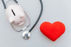 Στηθοσκόπιο εξοπλισμού γιατρών ιατρικής ή phonendoscope piggy τράπεζα και κόκκινη καρδιά που απομονώνονται στο άσπρο υπόβαθρο στοκ εικόνα