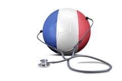 Στηθοσκόπιο με τη σφαίρα ποδοσφαίρου και τη σημαία της Γαλλίας Στοκ Φωτογραφία