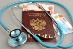 Στηθοσκόπιο με το διαβατήριο, τα χρήματα και το ιατρικό ασφαλιστήριο συμβόλαιο επάνω Στοκ φωτογραφίες με δικαίωμα ελεύθερης χρήσης