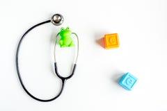 Στηθοσκόπιο, παιχνίδια στο τοπ πρότυπο άποψης υποβάθρου γραφείων γραφείων γιατρών παιδιών ` s Στοκ Φωτογραφία