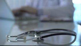 Στηθοσκόπιο που βρίσκεται στον πίνακα, γιατρός που λειτουργεί στο φορητό προσωπικό υπολογιστή στην αρχή, κλινική απόθεμα βίντεο