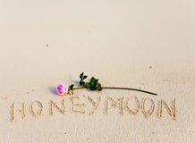 Στην άμμο ένας μήνας του μέλιτος επιγραφής και μια άνθηση αυξήθηκαν Στοκ φωτογραφία με δικαίωμα ελεύθερης χρήσης