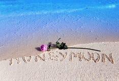Στην άμμο στην παραλία ένας μήνας του μέλιτος επιγραφής και μια άνθηση αυξήθηκαν Στοκ εικόνα με δικαίωμα ελεύθερης χρήσης