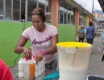 Στην αγορά, ο αφροαμερικάνος πωλεί το γάλα καρύδων με τον πάγο Κουίτο Ισημερινός στοκ εικόνες