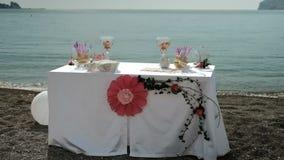 Στην ακτή υπάρχει ένας πίνακας με ένα λουλούδι για μια ρομαντική ημερομηνία απόθεμα βίντεο