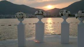 Στην ακτή υπάρχουν στήλες με τα λουλούδια στο υπόβαθρο του θερινού ηλιοβασιλέματος φιλμ μικρού μήκους