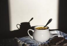 Στην επιτραπέζια μπλε πετσέτα με το σχέδιο διακοσμήσεων και τη σουπιέρα σούπας με την κίτρινη σούπα στο ήλιων σκοτεινό υπόβαθρο π Στοκ Φωτογραφίες