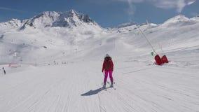 Στην κίνηση ο σκιέρ που κάνει σκι κάτω από την κλίση σκι στο θέρετρο βουνών απόθεμα βίντεο