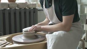 Στην κίνηση της ρόδας αγγειοπλαστών ` s ο κύριος στην ποδιά κάνει τα πιάτα με τα χέρια του απόθεμα βίντεο