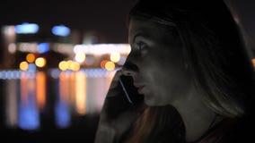 Στην ομιλία γυναικών οδών νύχτας στο κινητό τηλέφωνο Φω'τα πόλεων νύχτας υποβάθρου απόθεμα βίντεο