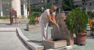 Στην οδό στην πόλη Perea, το νέο κορίτσι της Ελλάδας έρχεται στη στρόφιγγα και πλένει τα χέρια της απόθεμα βίντεο