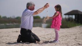 Στην παραλία, η εγγονή και ο παππούς, κοσκινίζουν την άμμο στα ο ένας του άλλου χέρια r απόθεμα βίντεο