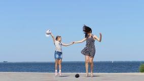 Στην παραλία mom και την κόρη, το όμορφο brunette στα sundress και τον έφηβο παιδιών κοριτσιών, χορός, που ακούει τη μουσική με μ φιλμ μικρού μήκους