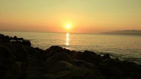στην παραλία ενάντια στην ανατολή μπροστά από την πέτρα απόθεμα βίντεο