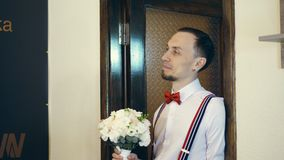 Στην πόρτα ο νέος τύπος μπαίνει, ο νεόνυμφος, σε έναν κόκκινο δεσμό τόξων και με μια ανθοδέσμη των λουλουδιών εξετάζει τη νύφη απόθεμα βίντεο