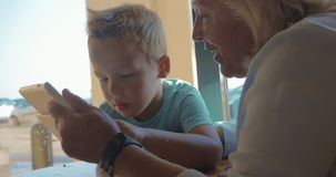 Στην πόλη Perea, η Ελλάδα κάθεται μια γιαγιά με τον εγγονό της και του διδάσκει πώς ταμπλέτα χρήσης απόθεμα βίντεο