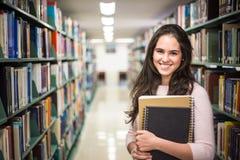 Στη βιβλιοθήκη - αρκετά γυναίκα σπουδαστής με τα βιβλία που λειτουργούν σε ένα χ Στοκ εικόνα με δικαίωμα ελεύθερης χρήσης