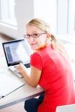 Στη βιβλιοθήκη - όμορφη, γυναίκα σπουδαστής με τα βιβλία και lap-top Στοκ φωτογραφία με δικαίωμα ελεύθερης χρήσης