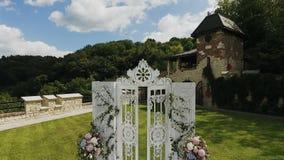 Στη γαμήλια τελετή φύσης στο πράσινο πάρκο Διακοσμήσεις για τη γαμήλια τελετή με την κίνηση ολισθαινόντων ρυθμιστών Γαμήλια αψίδα φιλμ μικρού μήκους