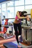 Στη γυμναστική Κουρασμένο μετά από το workout το κορίτσι βρίσκεται στον προσομοιωτή στοκ φωτογραφίες