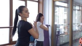Στη γυμναστική δύο νέες γυναίκες που κάνουν τα θερμά χέρια και το χαμόγελο φιλμ μικρού μήκους