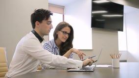 Στη γυναίκα γραφείων και μια εργασία ανδρών σε ένα γραφείο σε μια ταμπλέτα και ένα lap-top φιλμ μικρού μήκους