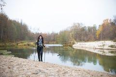 Στη λίμνη τραπεζών Σγουρή τοποθέτηση κοριτσιών μπροστά από τη λίμνη στο δάσος στοκ εικόνες