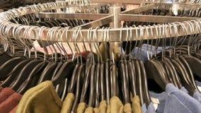 Στη μεγάλη στρογγυλή κρεμάστρα υπάρχουν διάφορα μοντέρνα πλεκτά πολύχρωμα πουλόβερ που κρεμούν στις μαύρες κρεμάστρες μόδας στο α απόθεμα βίντεο
