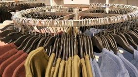 Στη μεγάλη στρογγυλή κρεμάστρα υπάρχουν διάφορα μοντέρνα πλεκτά πολύχρωμα πουλόβερ που κρεμούν στις μαύρες κρεμάστρες μόδας στο α φιλμ μικρού μήκους