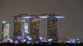 Στη Σιγκαπούρη, τη νύχτα, τα κτήρια ή οι πολυκατοικίες ενώνουν μαζί για να ανοίξουν την πυρκαγιά για να ενισχύσουν την ομορφιά τη στοκ εικόνες
