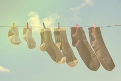 Στη σκοινί για άπλωμα ξεράνετε τις κάλτσες ολόκληρης της οικογένειας ενάντια στο μπλε ουρανό, τονισμένη φωτογραφία στοκ φωτογραφίες με δικαίωμα ελεύθερης χρήσης