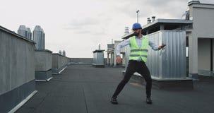 Στη στέγη του νέου όμορφου χορού αρχιτεκτόνων ή μηχανικών εργοτάξιων οικοδομής συγκινημένου φορώντας μια ασφάλεια απόθεμα βίντεο
