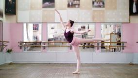 Στη χορεύοντας αίθουσα, το νέο ballerina στο μαύρο leotard εκτελεί 1 arabesque, αυξάνει το πόδι της επάνω πίσω κομψά, στάση απόθεμα βίντεο