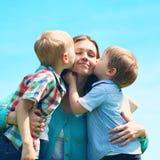 Στιγμή της ευτυχούς μητέρας! Οικογένεια δύο πορτρέτου γιοι παιδιών που φιλούν mom Στοκ Εικόνα
