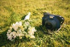 Στιγμιαία κάμερα με τη γαμήλια ανθοδέσμη στη χλόη Στοκ Εικόνα