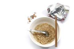 Στιγμιαία νουντλς με chopsticks, το κουτάλι και μερικά νομίσματα στοκ φωτογραφίες