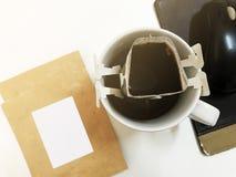 Στιγμιαίος καφές σταλαγματιάς στο άσπρο φλυτζάνι και συσκευασία στον άσπρο πίνακα γραφείων στοκ εικόνα με δικαίωμα ελεύθερης χρήσης