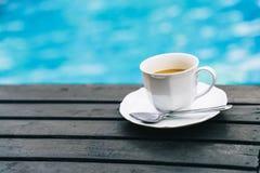Στιγμιαίος καφές στην ξύλινη επιτραπέζια πλησίον πισίνα στοκ εικόνες