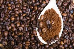Στιγμιαίος καφές στο κουτάλι στα φασόλια καφέ στοκ φωτογραφία