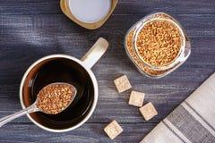 Στιγμιαίος καφές Φλυτζάνι με το κουτάλι ζεστού νερού και στιγμιαίου καφέ στον ξύλινο πίνακα στοκ εικόνα