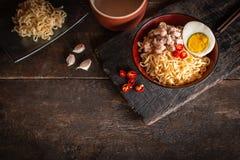 Στιγμιαίο νουντλς με το χοιρινό κρέας, αυγό και λαχανικά στο μαύρο κύπελλο στον ξύλινο πίνακα υπάρχουν τσίλι, chopstick, σκόρδο,  στοκ εικόνες
