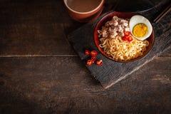 Στιγμιαίο νουντλς με το χοιρινό κρέας, αυγό και λαχανικά στο μαύρο κύπελλο στον ξύλινο πίνακα υπάρχουν τσίλι, chopstick και γυαλί στοκ φωτογραφίες με δικαίωμα ελεύθερης χρήσης