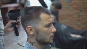 Στιλίστας με το hairdryer και χτένα στο barbershop απόθεμα βίντεο