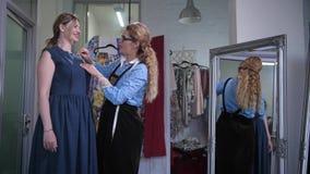 Στιλίστας που χαρακτηρίζει το neckline στο φόρεμα κατά τη διάρκεια της συναρμολόγησης απόθεμα βίντεο
