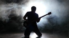 Στις ακτίνες των επικέντρων και της κιθάρας παιχνιδιού μουσικών καπνού απόθεμα βίντεο