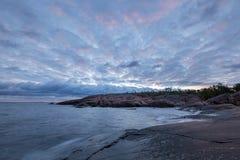 Στις αρχές νεφελώδους πρωινού στη δύσκολη ακτή θάλασσας Στοκ Φωτογραφίες