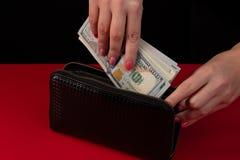 Στις γυναίκες τα χέρια ` s είναι το μαύρο πορτοφόλι δέρματος με ένα wad εκατό δολαρίων Επιχειρησιακή προσφορά στοκ φωτογραφίες